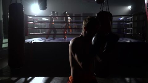 Guy beats a pear, in the background in the ring goes sparring kickboxers