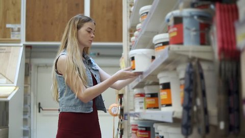 Young woman holding a tin of paint in a hardware store  woman buying paint  supplies for house painting  variety of cans on the shelf