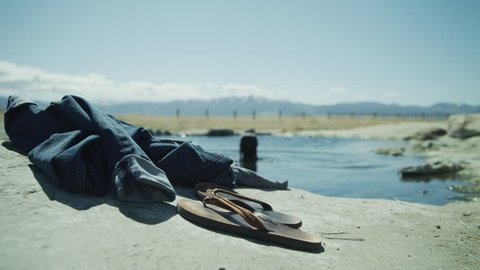 Close up of flipflops and jeans with woman skinny dipping in background / Meadow, Utah, United States