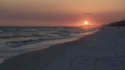 Dark orange sunset in Santa Rosa Beach, Florida, people silhouette walking in distance in panhandle with ocean gulf of mexico waves crashing, washing on shore, sun path reflection in slow motion