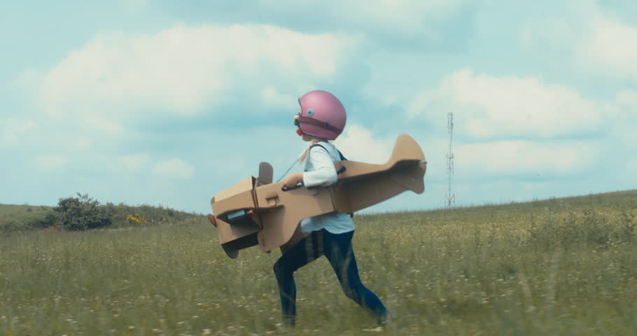 TRACKING Cute little dreamer kid girl wearing pink helmet and aviator glasses flying in a cardboard airplane through the field, pretending to be a pilot. 4K UHD 60 FPS SLO MO  #1014267215