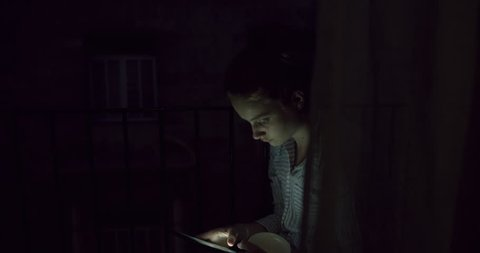 Young Woman swiping Smart Phone touch screen Device for social media behind Curtains at Night. Student Girl in Evening Light. A Bohemian Millenial