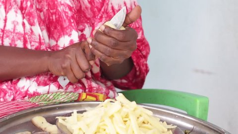 African woman sitting and carving potato in small pieces to prepare fried ..