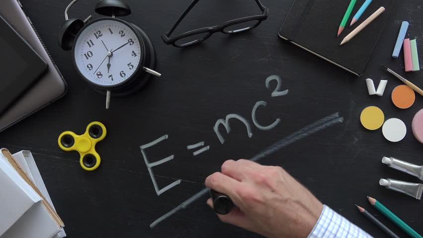 Teacher writing Albert Einsteins physical formula on school blackboard