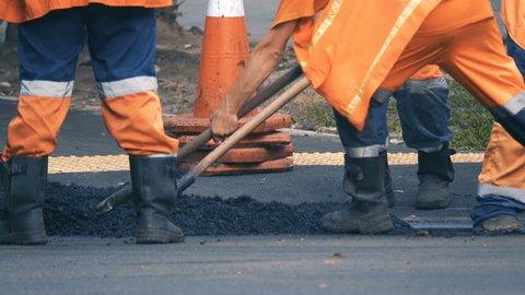Road workers lay asphalt