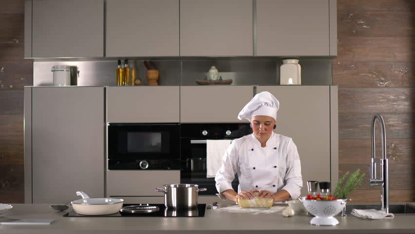 4K cooking footage, woman female chef cook in white cooks jacket preparing fresh dough for italian gnocchi in modern kitchen