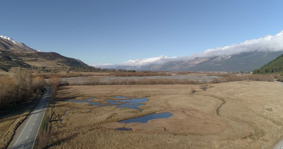 Aerial accending shot of a scenic valley with snowcapped mountains