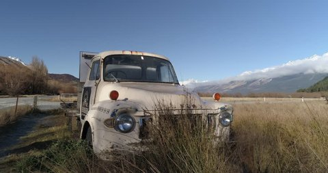 Aerial strafing reveal of old vintage truck in the tussocks in New Zealand