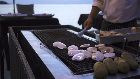 Grilled scallop on a charcoal grill by the beach.