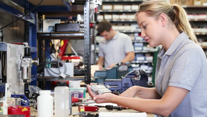 Engineer Helping Female Apprentice In Factory To Measure Component Using Micrometer