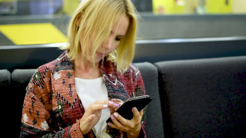 A middle-aged blonde woman writes in a mobile phone indoors. | Shutterstock HD Video #1014355895