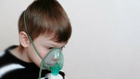Use nebulizer and inhaler for the treatment. Boy inhaling through inhaler mask. Side view.