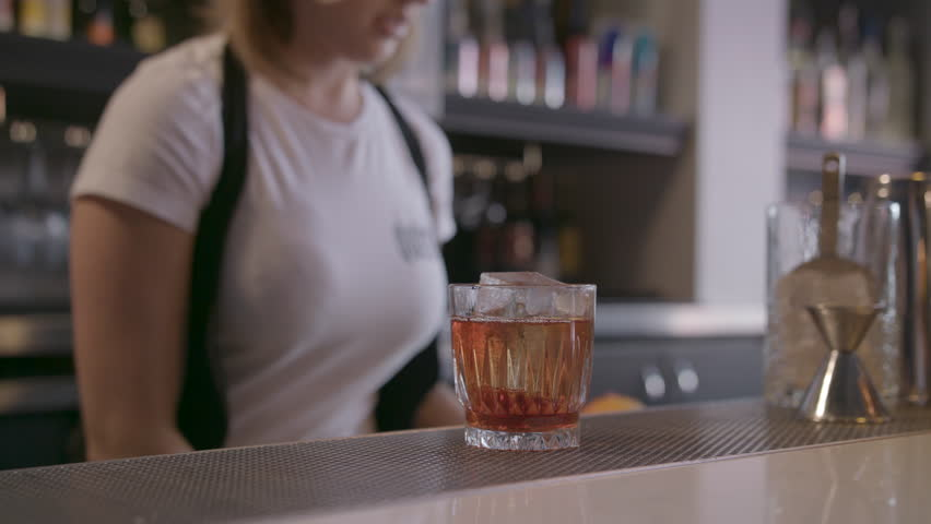 Close Up Female Bartender Cuts Orange Garnish for Cocktail in Slow Motion