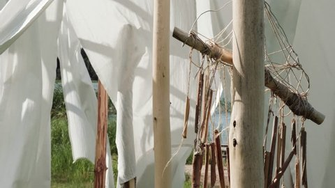 White linen cloth and ethnic dreamcatcher on wooden poles swings in the wind. Against the blue sky and green trees and fields.