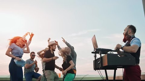 Low angle cheerful teenagers group jumping and dancing raising hands at summer rooftop party
