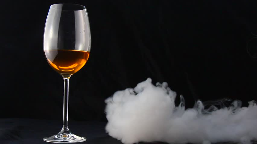 A glass of wine on a black background. a glass of wine in the smoke. | Shutterstock HD Video #1014373625