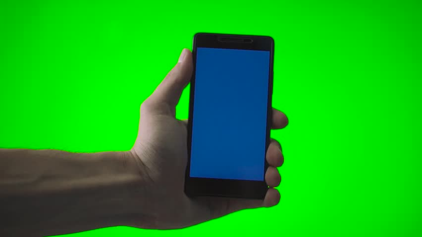 Arm of Slavic guy holding cellphone with blue screen. Hand of Caucasian man with smartphone on background of green screen. #1014376445