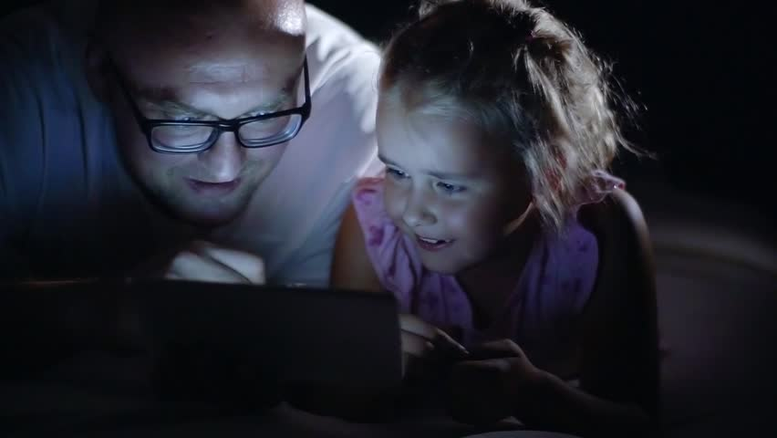 Happy family-father and daughter lying on the couch and using PC tablets at night. The family watches a movie on their tablet in a dark room.