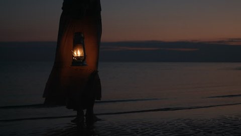 Girl in dress holding old kerosene lantern in her hand at beach after sunset at night