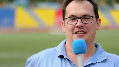 Man in glasses holds microphone and speaks near football field