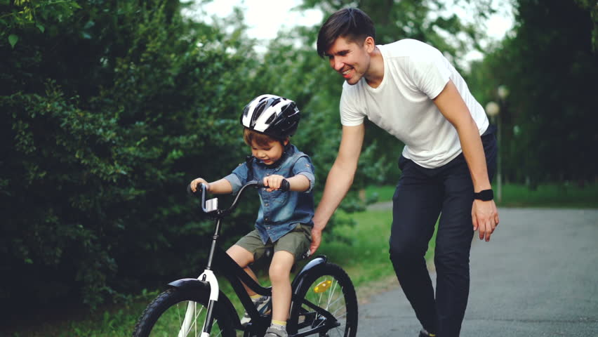 Slow motion of excited boy riding bicycle and laughing while his careful father is helping him holding bike and teaching child to ride. Family, sports and childhood concept. | Shutterstock HD Video #1014435365