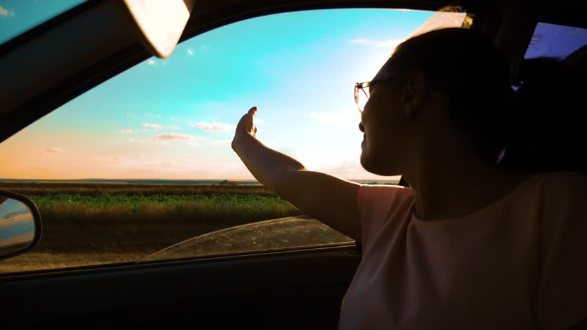 girl waving her hand in the window sunlight the wind In car slow motion video. Young happy young girl drives a car a holds her hand out from the window. Road trip, travel lifestyle and freedom concept