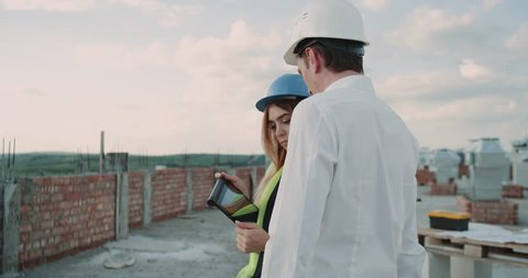 Woman expert engineers and her partner discussing the map of building using a tablet, the man speaking using a radio.