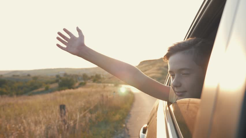 Teen boy looking out the car window and waving his hand.
