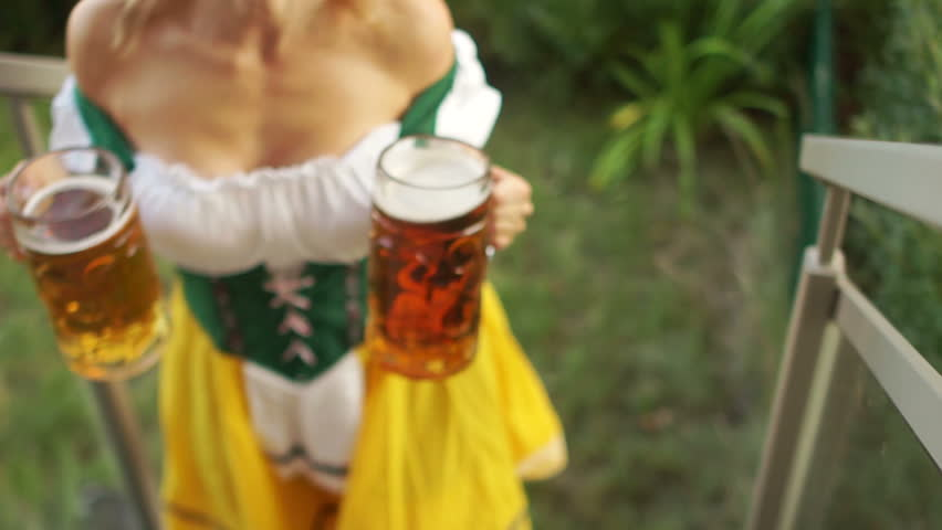 Sexy Oktoberfest waitress carries two large glasses of beer. The girl walks barefoot on the grass and climbs the stairs. Bavarian traditional costume, erotic neckline
