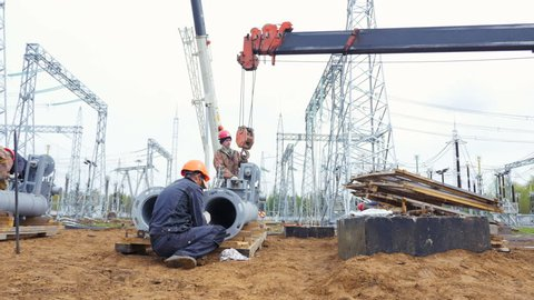 KAZAN, TATARSTAN/RUSSIA - MAY 29 2018: Skilled constructional fitter and erector fasten autocrane hook on large post pipe at transformer substation building site on May 29 in Kazan