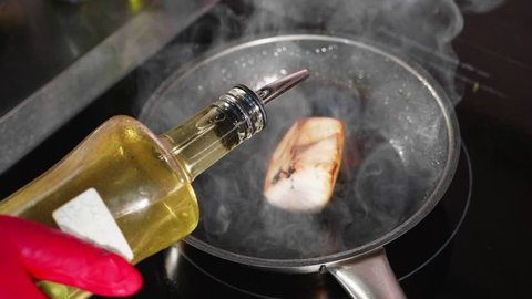 Pan-fried fish, The marlin fillet on the steaming frying pan in slow motion. Chef pouring a vegetable oil on the fish from glass bottle, above view.