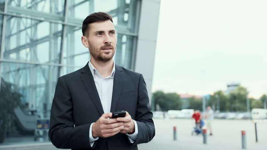 Handsome Businessman Chatting on his Smartphone While Exiting the Big Building. Checking News, Mails.Looking Confident, Successful. Classically Dressed. Walking in the City. | Shutterstock HD Video #1014544445
