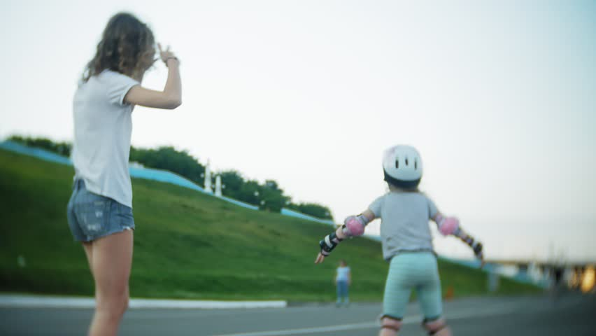 Mom and daughter ride on roller skates. Girl learning to roller skate, and falls. Mom teaches daughter to ride on rollers 4k