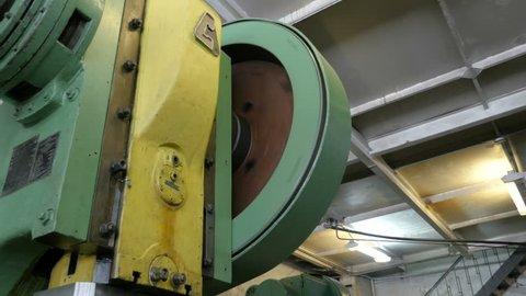 Rotating a big flywheel in a workshop at a plant.