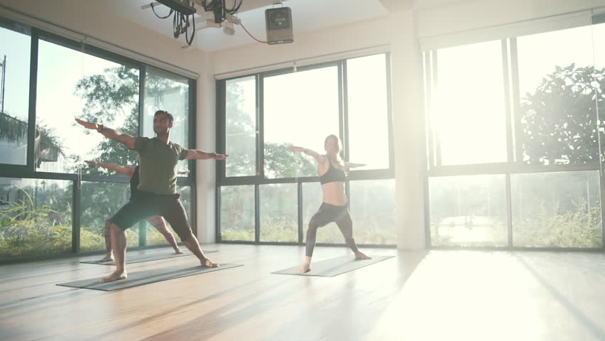 People practice warrior II yoga pose in studio high key shot rapid slow motion