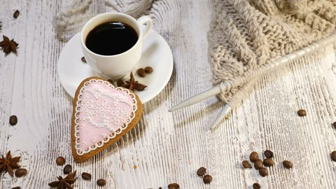 Love concept. Saint Valentine Day. a cup of fresh brewed coffee and a heart shaped ginger cookie on wooden background. Female hand places an arrow shaped cookie near