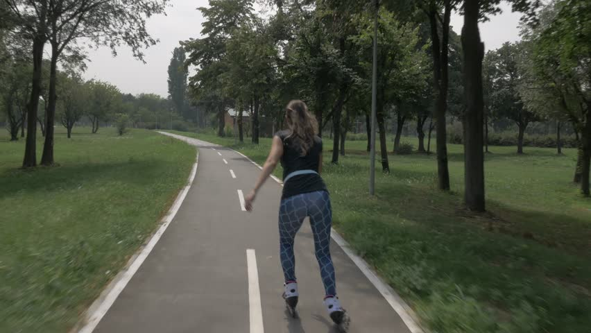 White handsom brown hair girl in tight blue pants woman riding roller skates on bike road in park, during summer day
