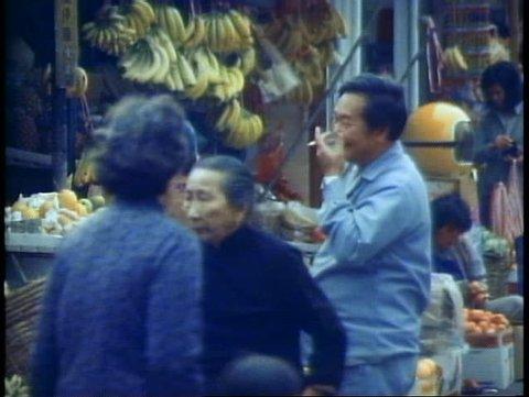 HONG KONG, CHINA, 1982, Street market, bananas, man smoking, fish hanging