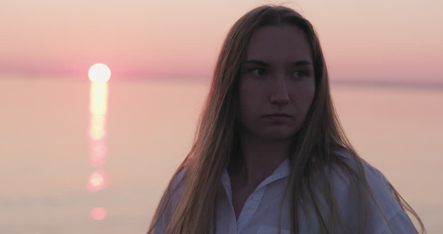 Slow motion handheld teenage girl turns around and having fun with her hair on a beach at sunset #1014594905