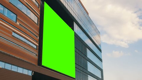 Green screen billboard or large display on shopping mall building in city center. Entertaiment, consumerism and chroma concept. Timelapse shot with moving clouds