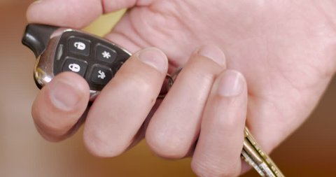 Man setting a car alarm security system by pushing the lock button on a remote control - close up