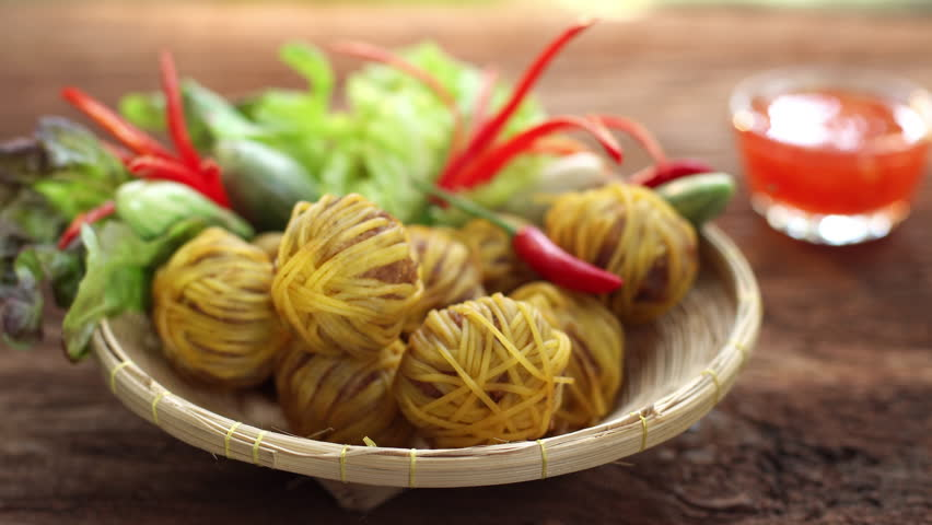 Thai tradition food: Moo Sarong is Pork mix with herbs and warpped with yellow noodles then deep fried, Served with sweet sauce  Famous food of Thailand. Shoot in studio, Clean food good taste concept