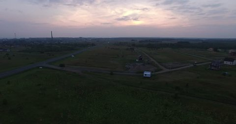 4K aerial video of green fields and highway on dark summer evening near huge Plesheevo Lake in outskirts of historical town of Pereslavl-Zalessky in Yaroslavskaya oblast north-east of Moscow, Russia