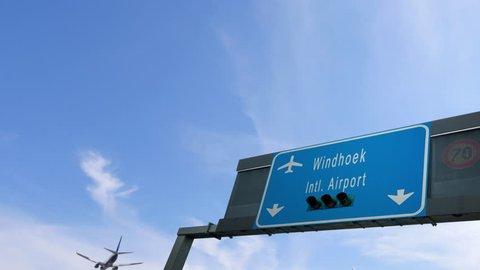 airplane flying over windhoek airport signboard