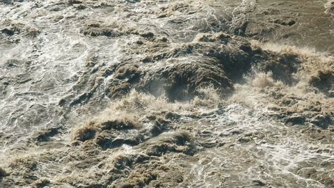 Beautiful Natural Slow Motion Torrent of a Stormy Mountain River. Flash Flood Muddy River. Rushes River Raging Fast Flowing Water. Natural Disasters Stormy Brown Turbid Water Flow