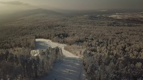 top view of the Russian Chelyabinsk forest: trees, fields, ski resort, descent and ski lift