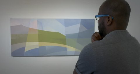 MCU African American man looking thoughtfully at abstract landscape painting in art gallery. Tripod shot from over the shoulder