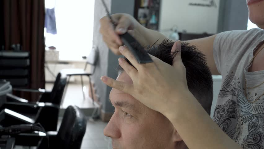 Woman hairdresser cuts hair of a man in a beauty salon. She combs her hair with a comb and cuts it with scissors. Hair care. Side view. 4K, 25 fps.