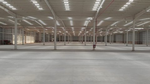 Aerial interior clip of an empty warehouse with camera moving forward and rotating 360 degrees
