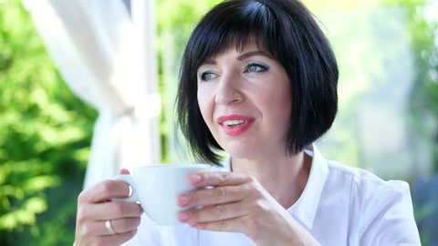 Portrait of pleasant smiling, Happy beautiful real 40 years old Ukrainian woman. a woman drinking coffee, tea , from a white cup.